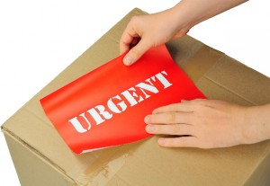 hands placing label on parcel for urgent delivery